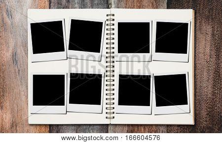 Blank classic film photo frame on photos album, on wooden desk