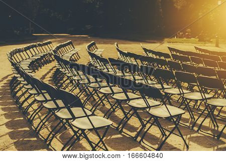 Empty seat rows of folding chairs on ground before a event parallel and rounded arranged multiple black chairs on street on sunny day in park with people on grass meadow in distance
