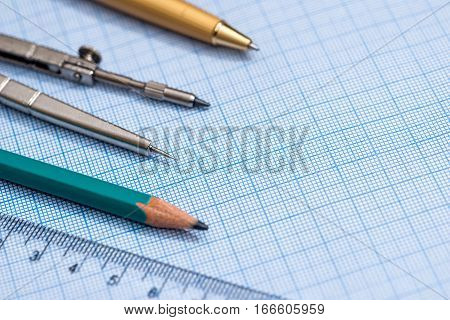 drawing compass pencil and ruler on graph paper background