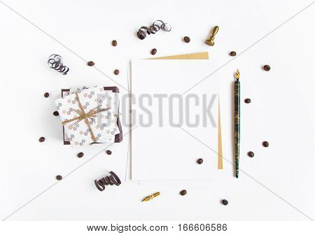 Pile of rustic handmade gifts and a letter on white background decorated with serpentine streamers and coffee beans. Rustic style cute paper DIY decoration. Any holiday concept. Flat lay top view