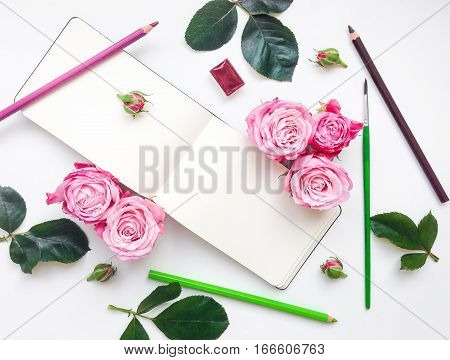 Colorful composition with sketchbook roses watercolors and pencils. Flat lay on white table top view