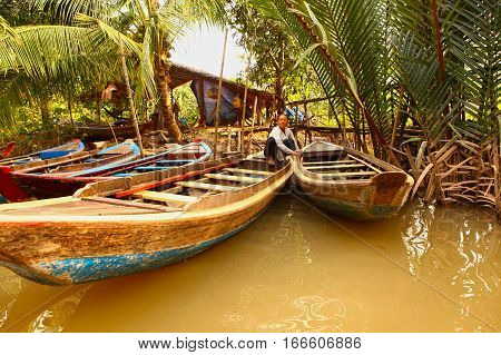 Mekong river Vietnam December 27 2016: Unidentified vietnamese wonam with canoe on the Mekong river shore with boats after hard working day in Vietnam December 27 2016.