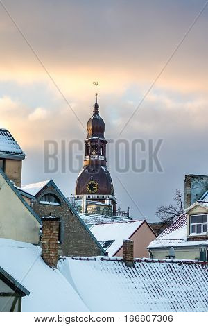 View on Old Riga roofs and Saint Peters Church tower on sunset. Saint Peters Church is a tall Lutheran church in Riga, Latvia
