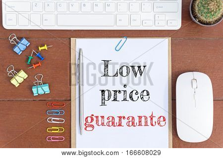 Text Low price guarantor on white paper which has keyboard mouse pen and office equipment on wood background / business concept.