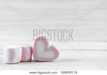 Candy hearts on a white wooden table / heart represents love in Valentine's Day / wedding day.