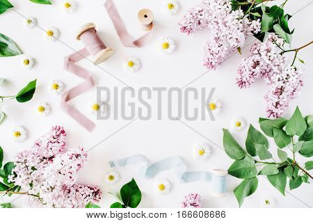 Floral frame of lilac flowers chamomile fresh branches and spool with blue and beige ribbon on white background. Flat lay top view