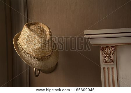 Stylish straw hat is hanging on the lamp . The window light falls on the left side to the straw hat and fireplace