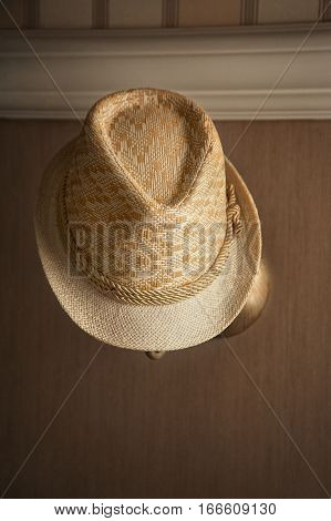 stylish straw hat is hanging on the lamp . The window light falls on it on the right side