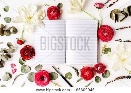 Workspace. Notebook or sketchbook pink and red roses or ranunculus white tulips and green leaves on white background. Flat lay top view