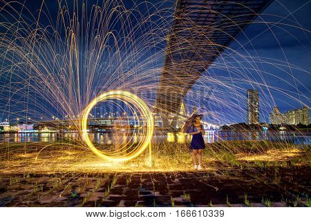 Beautiful woman with umbrella and hot golden sparks rain from man spinning burning steel wool under Bhumibol Bridge in Bangkok Thailand. Long Exposure Photography using Steel Wool Burning.