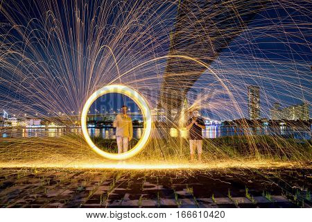 Hot Golden Sparks Flying from Man Spinning Burning Steel Wool under Bhumibol Bridge in Bangkok Thailand. Long Exposure Photography using Steel Wool Burning.