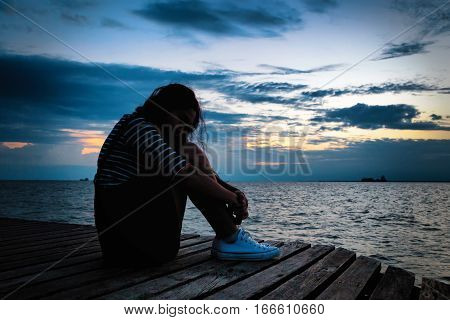 Beautiful Woman In Frustrated Depression Sitting On Wooden Bridge, Near The Beach On Sunset. Concept
