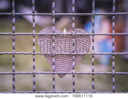 Tinkered and self made heart hanging behind a grid fence