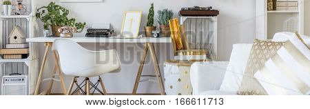 Boho style home workspace with white chair and simple desk poster