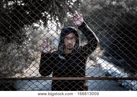 Depressed Man Wearing A Black Hoodie Standing Behind A Fence Hand Grabs Steel Mesh Cage, No Freedom