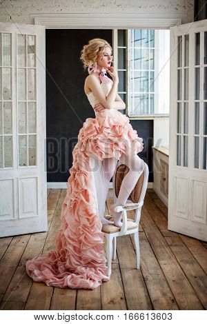 Fashion photo of beautiful girl wearing high and low dress. Professional make-up and hairstyle. Perfect skin. Fashion photo. Baroque style.