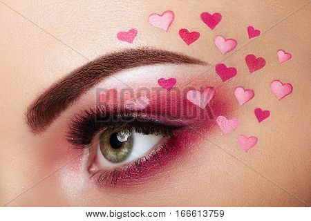 Eye make-up girl with a heart. Valentine's day makeup. Beauty fashion. Eyelashes. Cosmetic Eyeshadow. Makeup detail. Creative woman holiday make-up