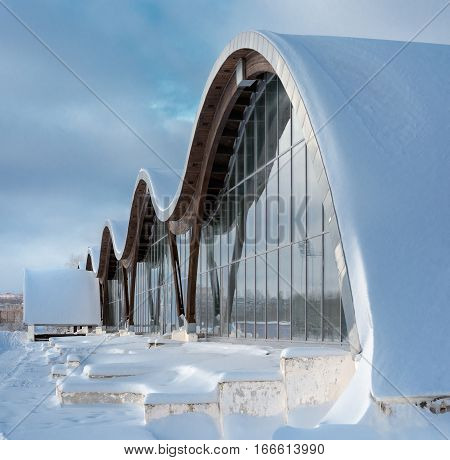 MINSK BELARUS - January 15 2017: Sports complex Olympic reserve. Pool National Olympic Training Center in athletics in Minsk Belarus. Element of modern building with wave shape facade against blue clear sky. Design of arched roof and stained glass system.