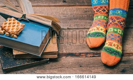 Feet of person wearing colorful winter socks reading book and eating cookies