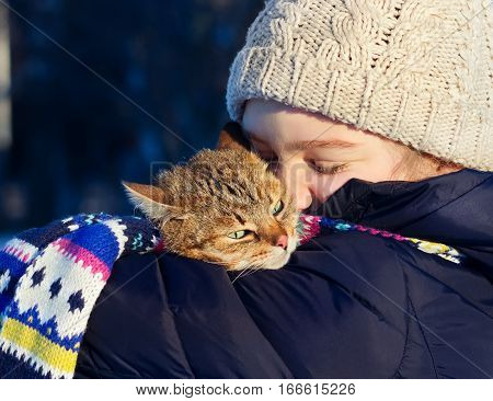 Outdoor portrait of a young happy girl holding her red cat in winter park.
