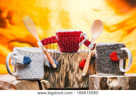 Pair of big and one small tea mugs in knitted sweaters on wooden stands. Concept of family tea time