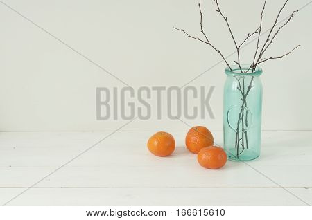 Minimal elegant composition with tangerines and turquoise vase