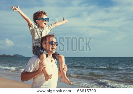 Father and son playing in the park at the day time. People having fun on the beach. Concept of friendly family and of summer vacation.