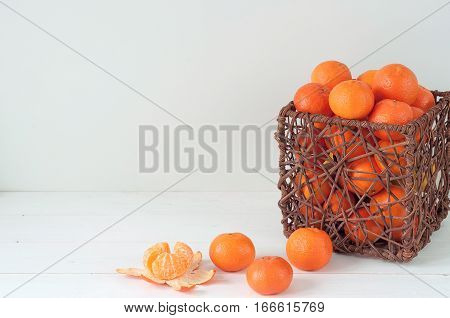 Minimal elegant composition with tangerines and wood basket