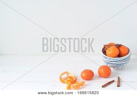 Minimal elegant composition with tangerines and cinnamon on white