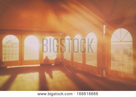 Sunlight in an empty tent on the sandy beach of the Baltic sea with silhouettes of people on the background