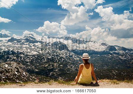 Young Girl Sitting On The Ground In Mountains Dachstein Krippenstein In Austria