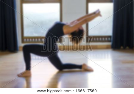 Young woman practicing yoga in a yoga studio. Modern blurred image. Abstract blur sports background.