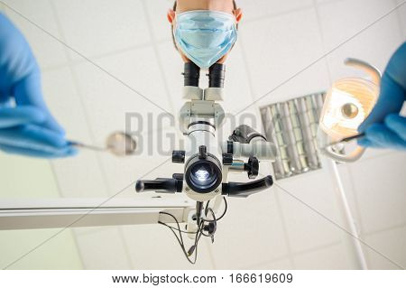 Doctor With A Microscope In A Dental Clinic