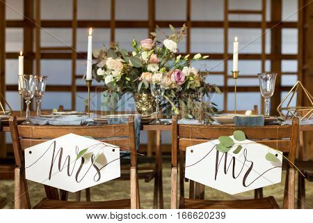 Wedding party. Laid Table by wedding banquet in a wooden barn. Candles and bouquet. Vintage Style.
