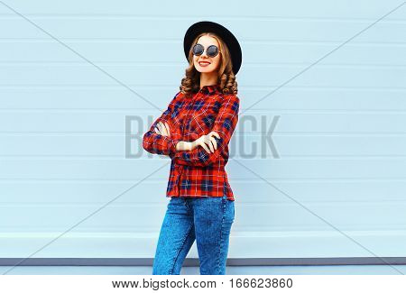 Fashion Pretty Young Smiling Woman Wearing A Black Hat, Red Checkered Shirt Over Blue Background