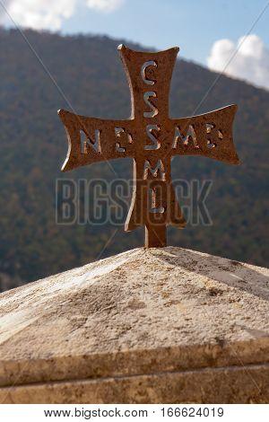 A rusty cross statue in a Saint Benedict Abbey
