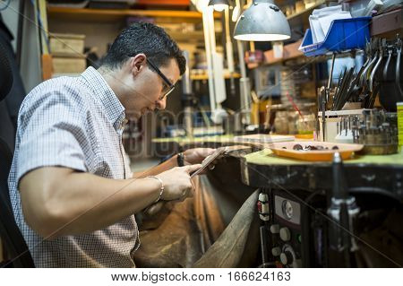 Goldsmith crafting jewelry with many tools in an atmospheric enironment