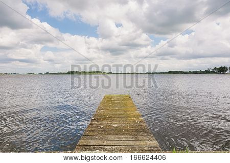Small dock and seagulls in the lake near the small Dutch town Giethoorn.