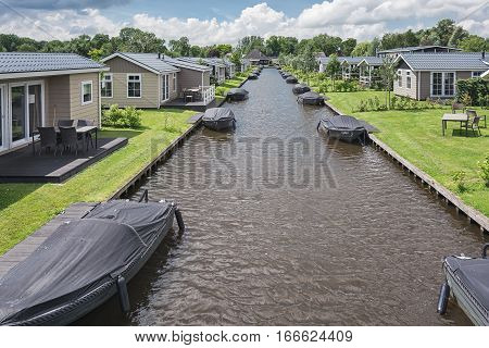Giethoorn Netherlands - June 29 2016: Canal with moored boats near the bungalow.