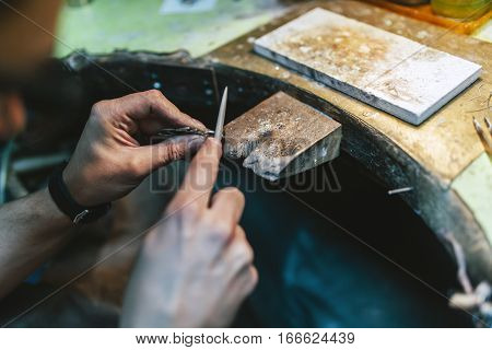 Young goldsmith working and creating new jewelry