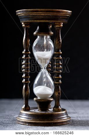 still life with old hourglass on dark background