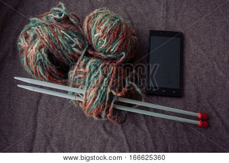 holidays lifestyle hobby concept- photo ball of yarn with knitting needles. Clews of colored wool yarn. Closeup photo