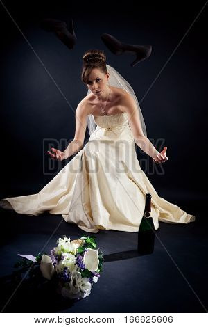 a desperate bride sitting down and throwing her shoes in the air.