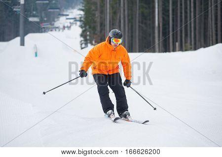 Skier Skiing Downhill At Ski Resort Against Ski-lift