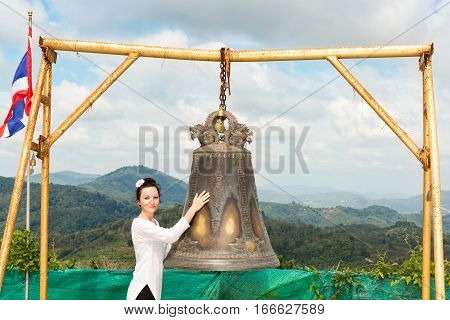Woman near Thai gong in Phuket. Tradition asian bell in Buddhism temple in Thailand. Famous Big bell wish near Gold Buddha