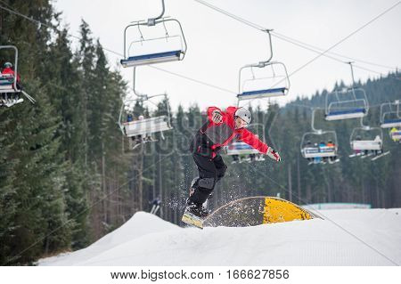 Snowboarder Flying Down From A Hurdle In Winter Day