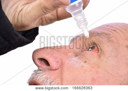 Senior Man Dripping A Red Eye With Eye Drops