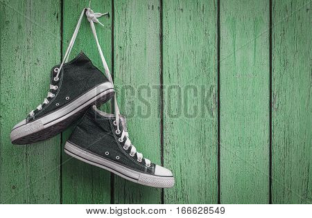 Wearing a pair of blue sneakers hanging on a nail the empty space