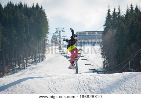 Female Boarder On The Snowboard Jumping Over The Slope