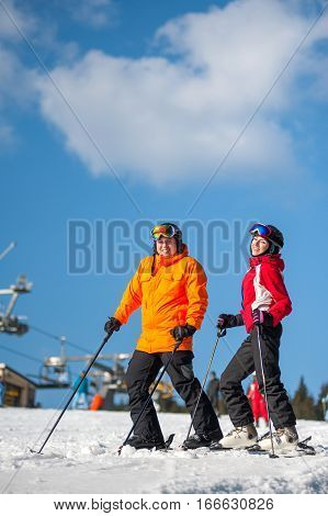Man And Woman Skiers With Skis At Winter Resort